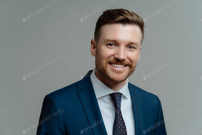 Happy successful entrepreneur in suit smiling at camera while posing against grey background