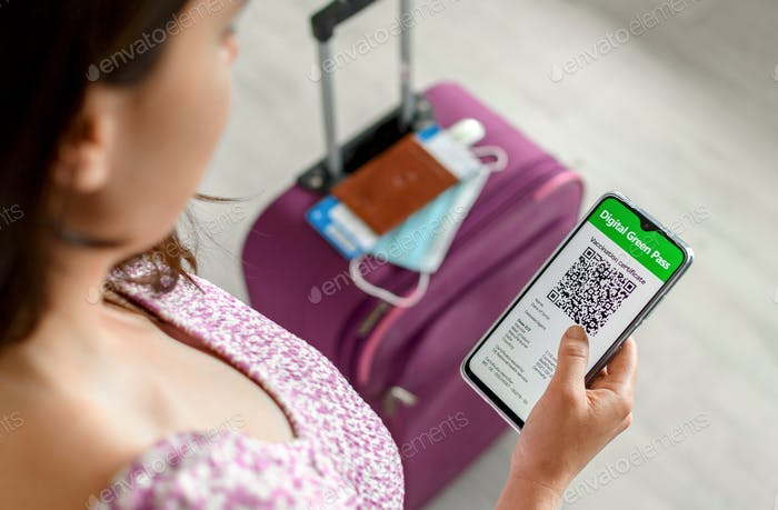 Top view of woman holding identification documents vaccine certificate on smartphone at airport.