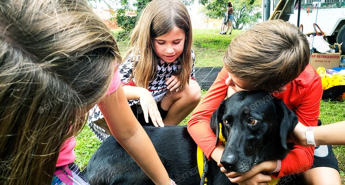 Kids in a family gathering around humane society dog to give some love and a new home