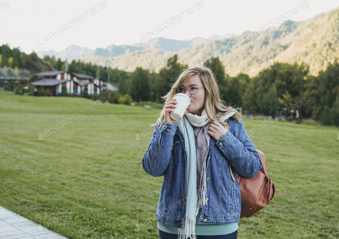 Young blonde woman in jeans coat  with paper cup of morning coffee at the chalet cottage village