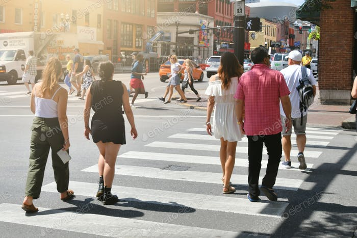 Downtown Nashville TN with traffic and Lower Broadway in the background and people crossing street