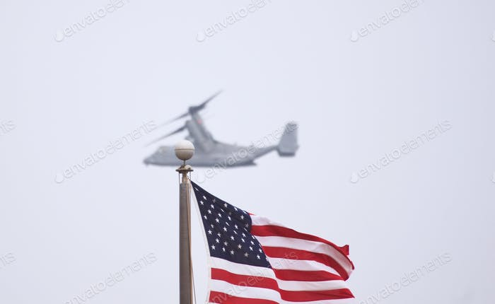 Marine Osprey flying past the flag of the United States of America.