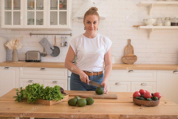 Woman cutting avocado.