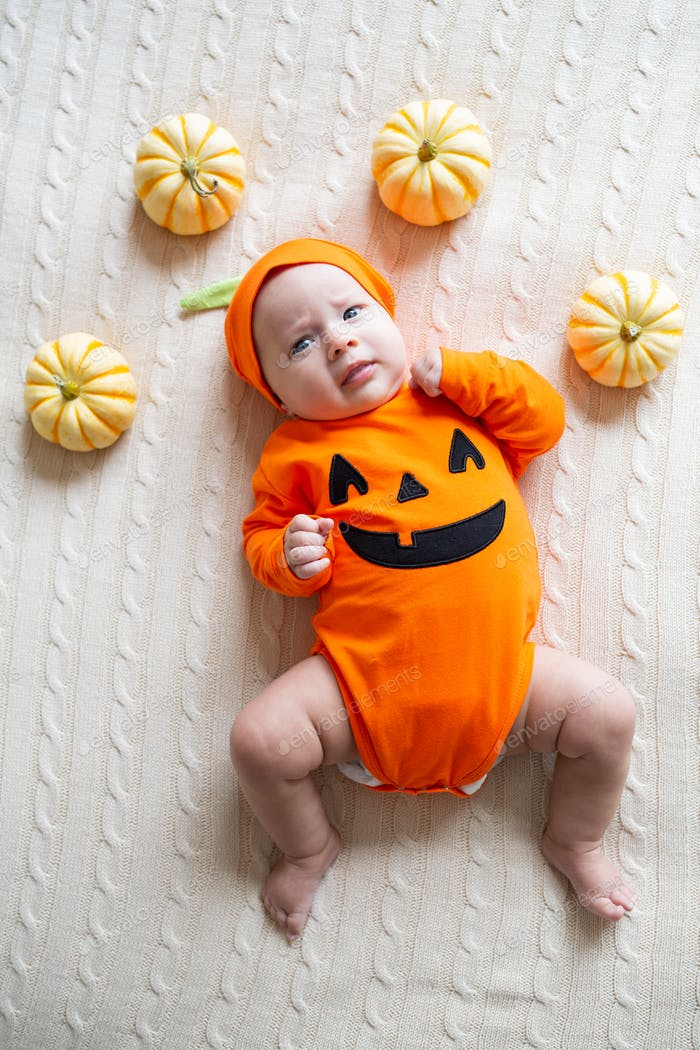 Cute baby girl three months old wearing funny orange costume for celebrating her first Halloween