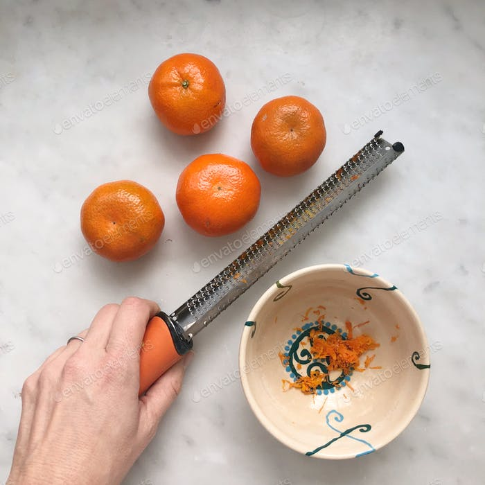Zesting oranges with a grater in the kitchen