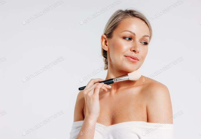 Beauty portrait of blonde smiling woman 35 year plus holding blush brush near clean fresh face
