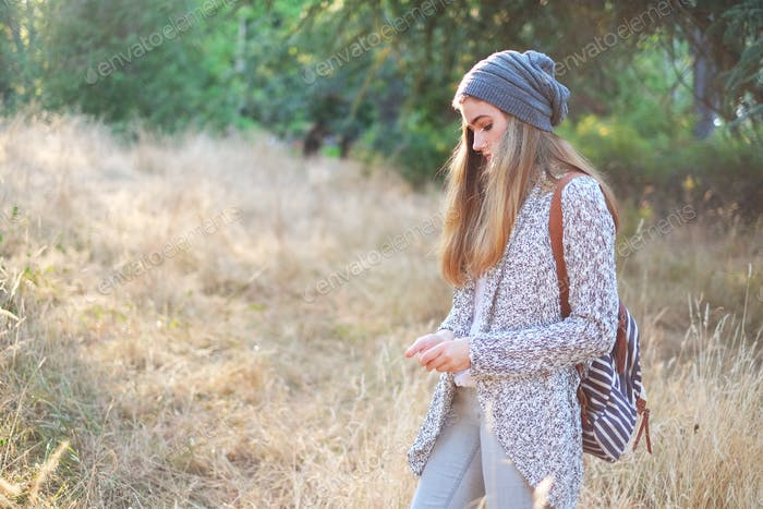 Teenage girl standing in a dried grass field