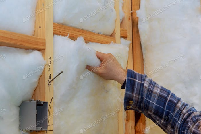 Worker in insulating rock wool insulation in wooden frame for future house walls for comfortable