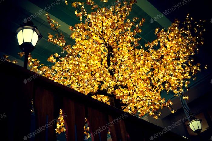 A bright gold illuminating tree indoors.