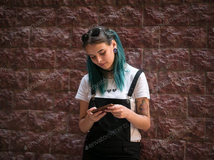 Portrait of Young girl with blue hair using mobile device