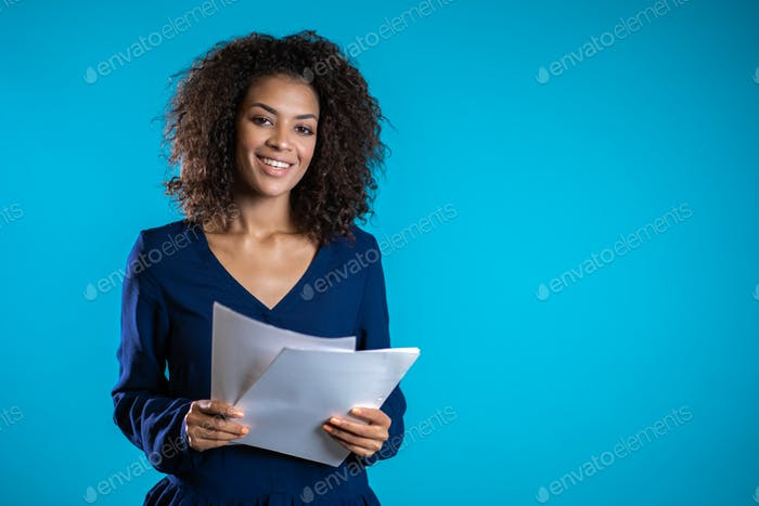 Pretty african american female boss checks documents, utility bills