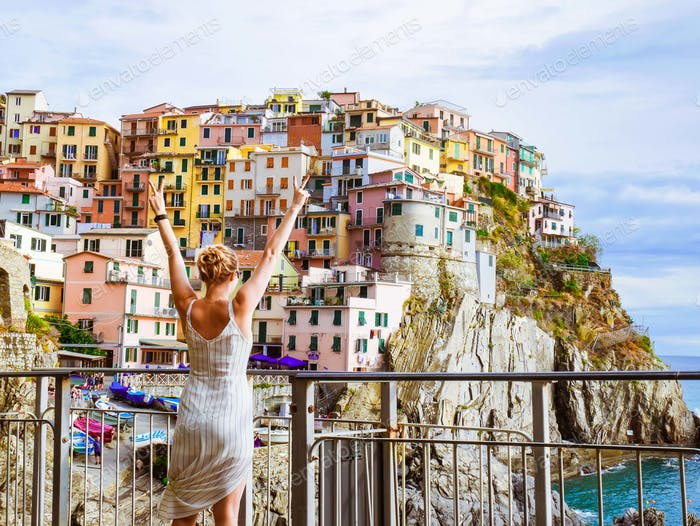 Gril doing the peace sign in front of colourful houses in Manarola, Cinque Terre