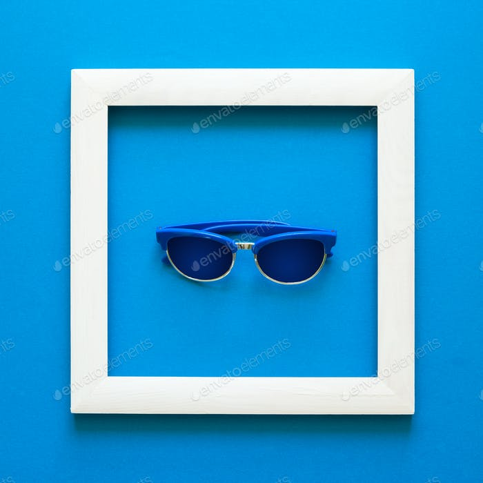 Minimalismus. Meisterwerk im Holzrahmen. Sonnenbrillen Ansicht von oben Flach legen. Konzept des Sonnenschutzes.