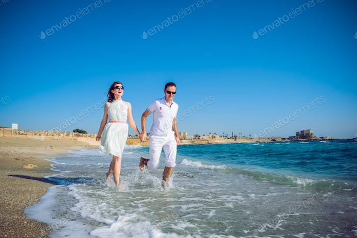 Young  happy Couple holding hands, enjoying Romantic Beach Holiday and  on a sandy beach