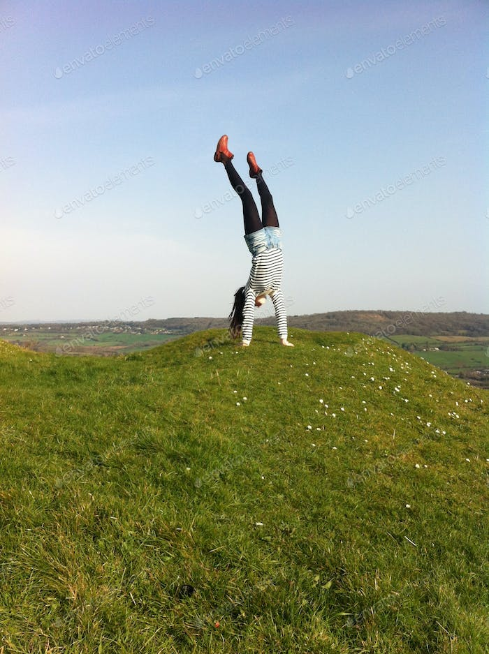 Girl doing a handstand on a hill