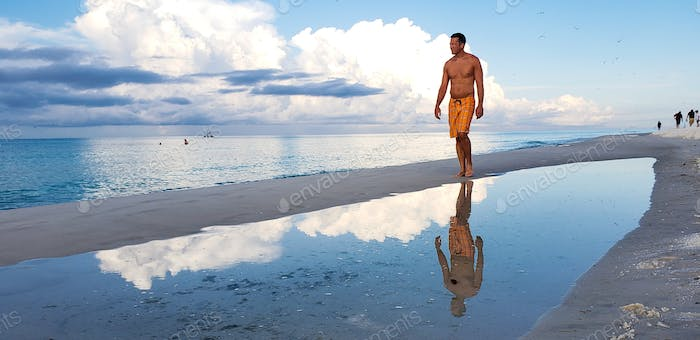 Millennial man walking down the beach in the summertime thinking through the clouds and thinking