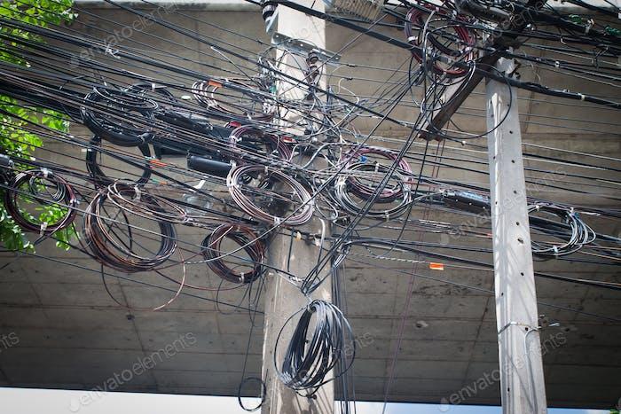 Unordentliche Drähte, die am elektrischen Mast befestigt sind. Das Chaos von Kabeln und Leitungen an einem elektrischen Pol.