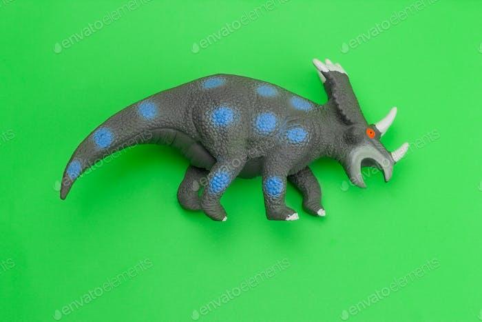 lustiges Dinosaurier-Spielzeug auf grünem Hintergrund