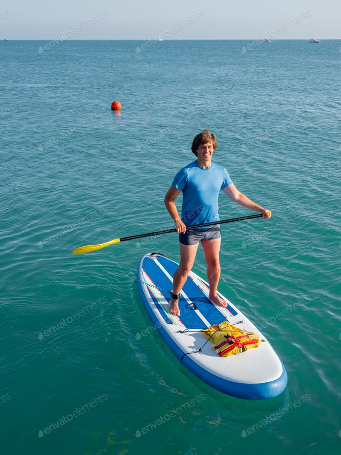 Paddle boarder. Sportsman paddling on stand up paddle board. SUP surfing. Active lifestyle.