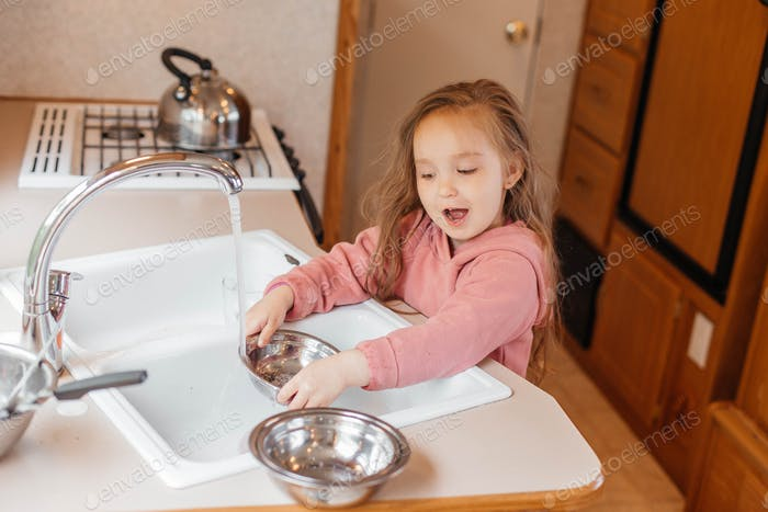 A little girl washes the dishes in the kitchen in the motorhome. Happy childhood concept