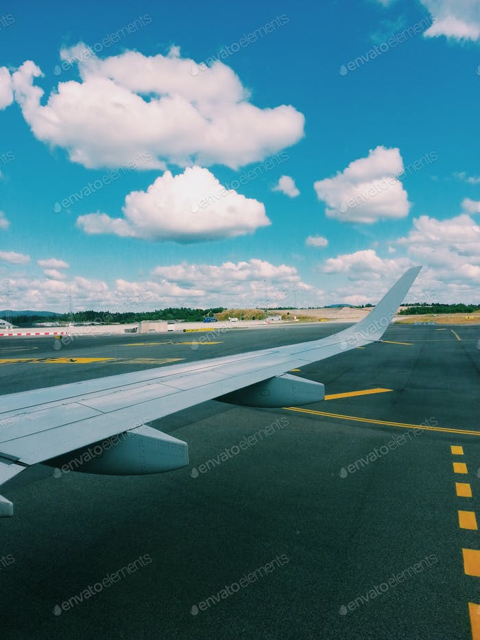 Summertime : airplane on the tarmac, ready for departure, blue sky, horizon over land, airplane wing