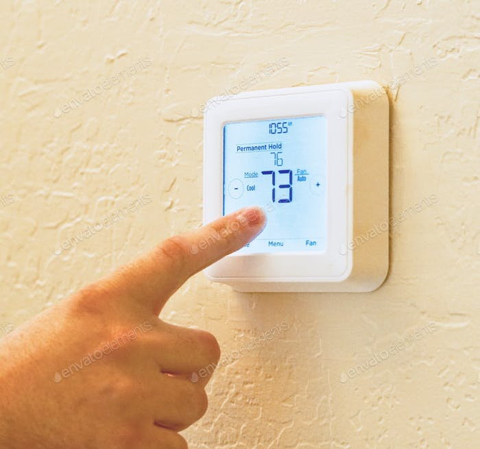 Adult male finger on a thermostat adjusting the temperature