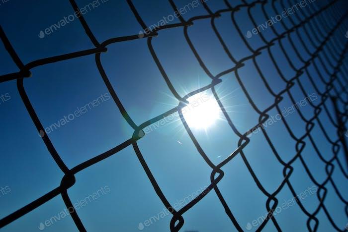 Blick auf die Sonne durch einen Kettengliederzaun.