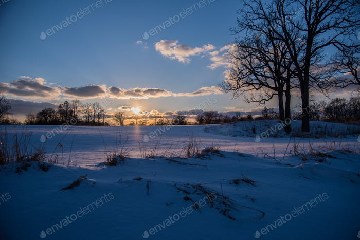 Sunset on icy blue winter landscape