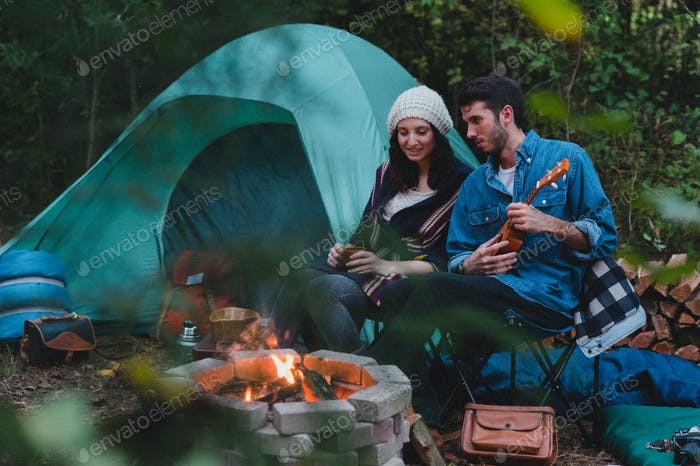 Attractive young couple sitting by a campfire and tent.