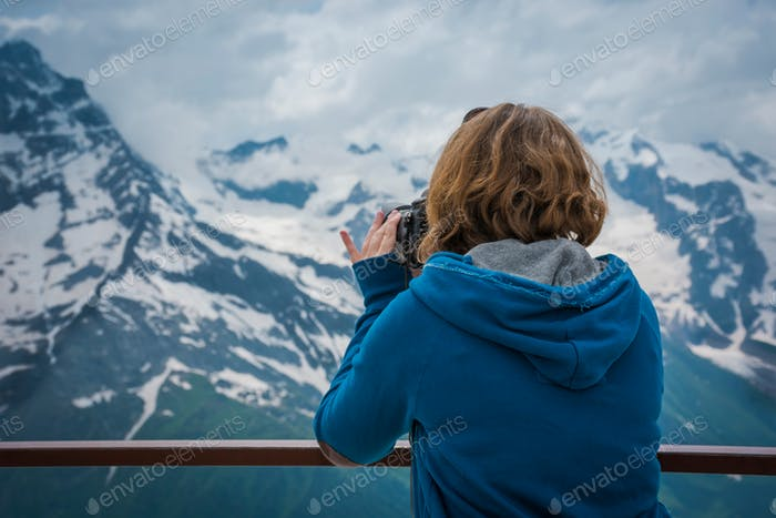 A girl takes pictures of mountains.