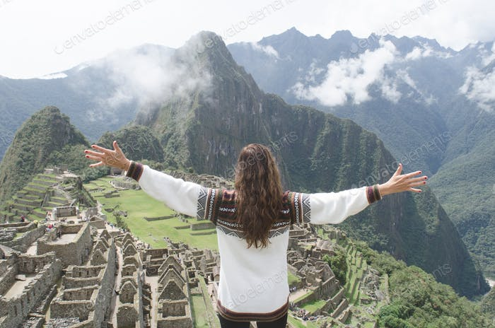 A young woman traveling alone looks out at Machu Picchu with her arms spread wide open