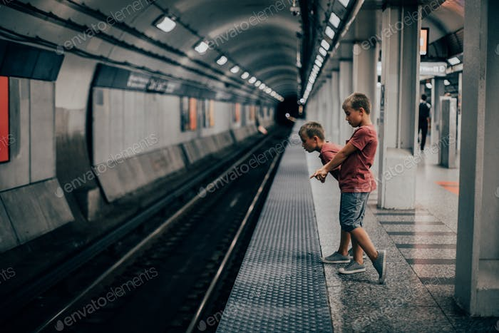 Twin boys looking at the rats, and coin on the Chicago CTA, waiting for the train. First time in Chi
