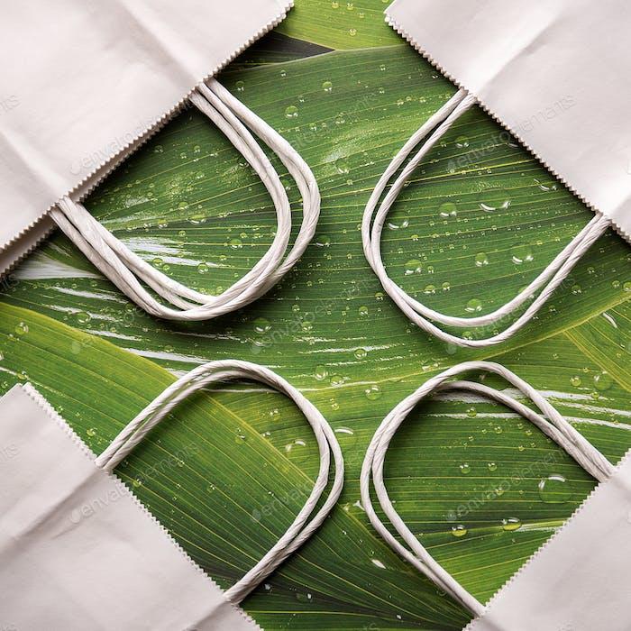 Umweltfreundliche Papiertüten auf grünem Blatthintergrund, Minimalismus, minimal