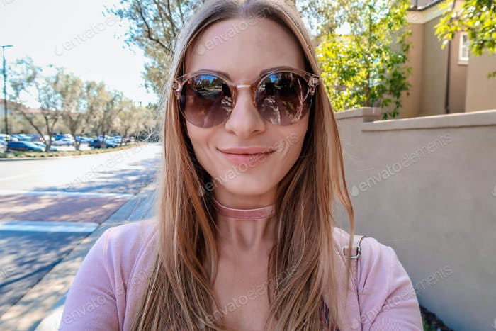A girl in sunglasses makes selfie and smiling