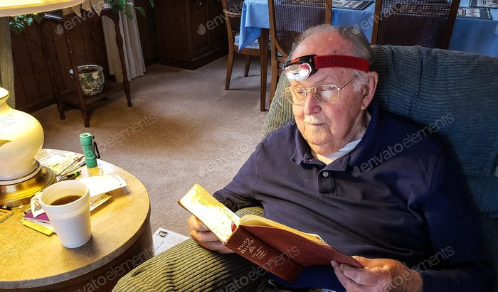 Senior citizen relaxing at home reading his bible with the help of lighted headgear to supplement