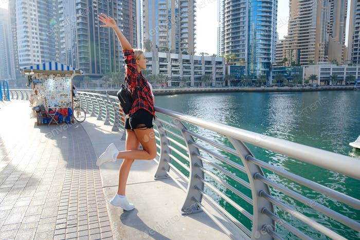 Young blonde traveler woman walking on the street outdoors in Dubai city
