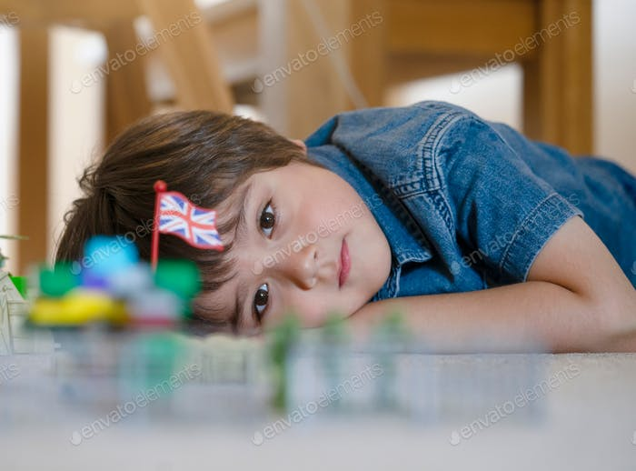 Selective focus of little boy lying on floor looking out deep in thought