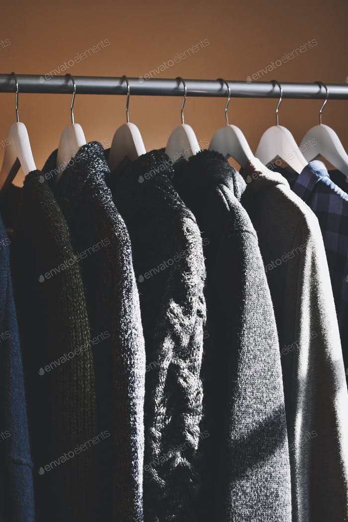 Closeup of warm woolen sweaters hanging to clothes rack