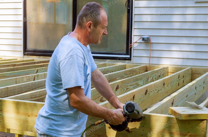 Installing of wooden deck patio carpenter hammering on a deck patio