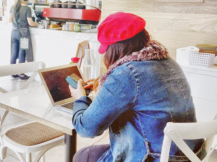 Cafe lifestyle - fashionable millennial woman in red cap and faded denim jacket, using both mobile p