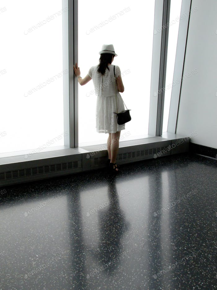 Fashionable woman dressed in style standing by floor to ceiling windows with reflection on ground