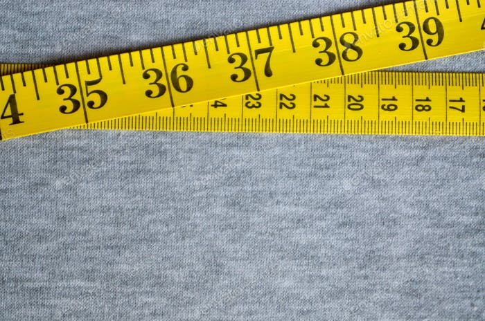 The measuring tape of yellow color with numerical indicators in the form of centimeters or inches
