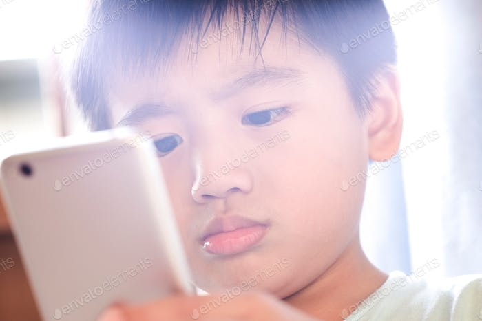 Close-up portrait of a young kid using smartphone with lens flare