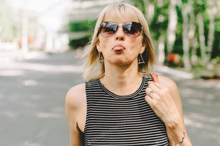 Portrait of happy mature adult woman making faces sticking her tongue out. Senior shows her tongue a