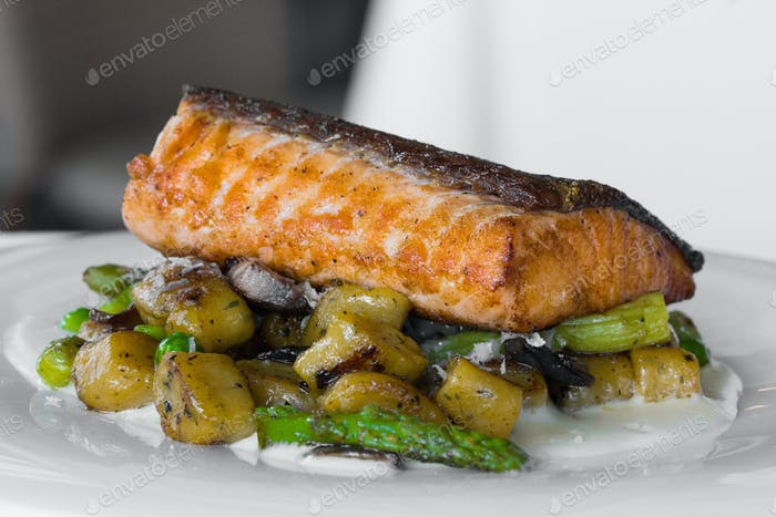 Pan Seared Salmon with gnocchi, wild mushrooms, roasted tomatoes and parmesan sauce