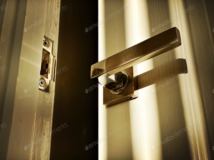 A close up low angle view of a modern lever handle on a gloss white door slightly ajar with dark and