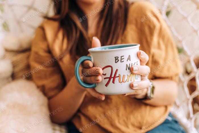Woman having coffee in mug that reads be a nice human