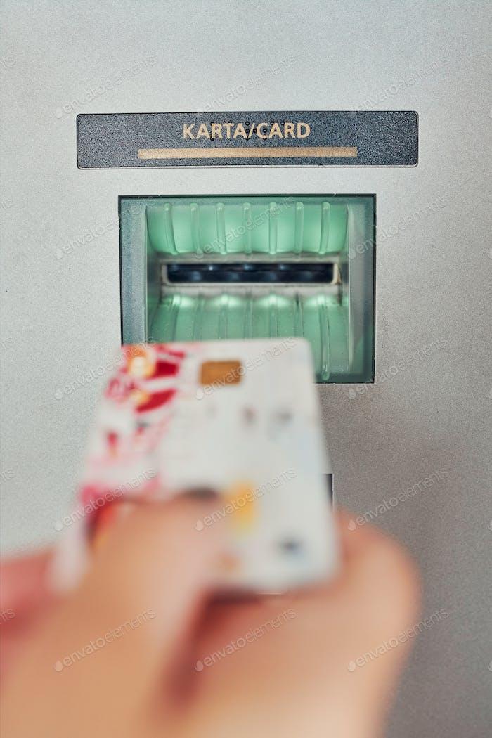 Frau zieht Geld vom Geldautomaten ab und legt Kreditkarte in das Geldautomaten-Terminal