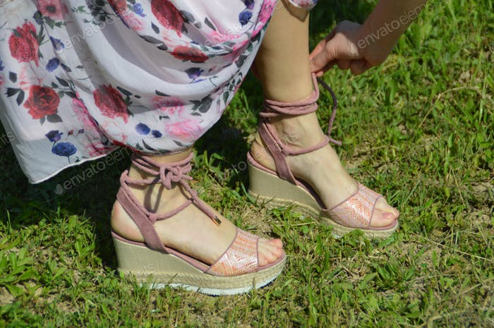 Cropped photo of woman's feet in sandals standing in grass