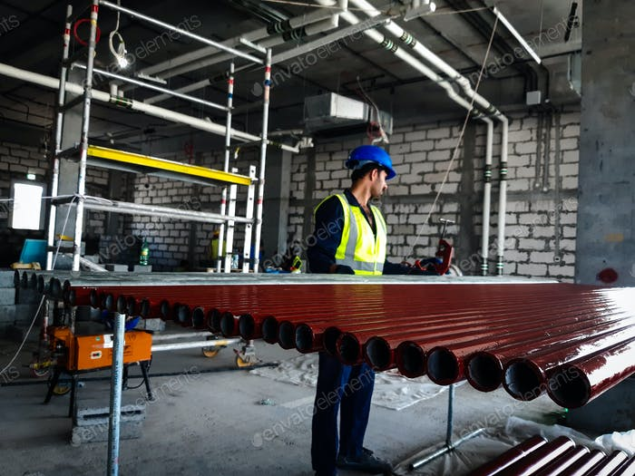 Construction site worker arranging the materials , firefighting equipment installation